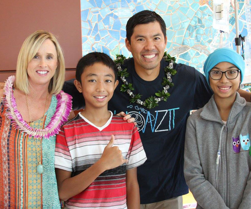 Kurt and Renee Suzuki flash a smile with two young patients at Kapiolani Medical Center.