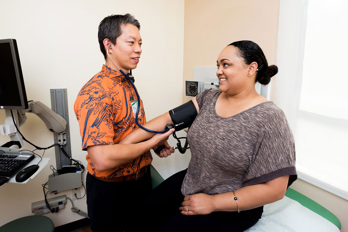 Dr. Jason Pirga reads a female patient's blood pressure in a clinic at Straub Medical Center