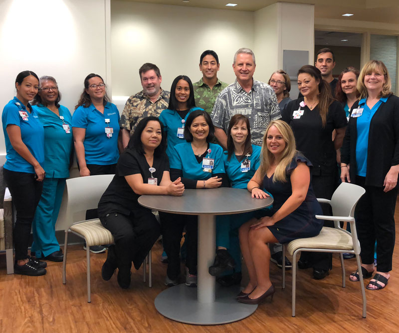 "Hawaii News Now ""Sunrise on the Road"" reporters Dan Cooke, Steve Uyehara and Howard Dicus pose for a group shot with staff members from the Pali Momi Infusion Center"