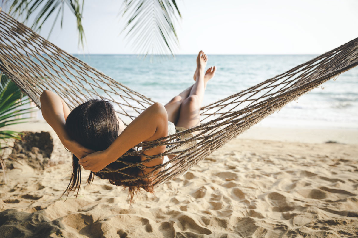 a woman relaxes in a hammock by the beach