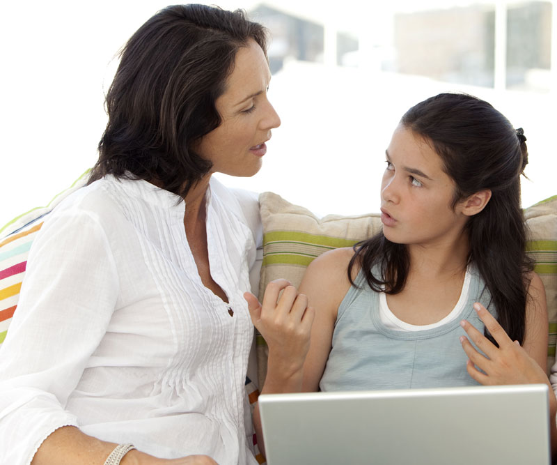 a teenage girl talks with her mother about a website on a computer