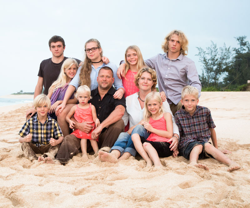 Casey Schmidt sits on a beach with her husband and nine children
