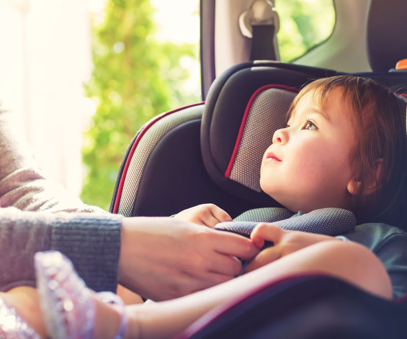 young child getting buckled into a car safety seat