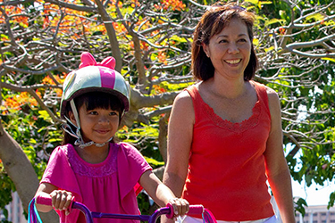 mother and daughter riding her bike in the park