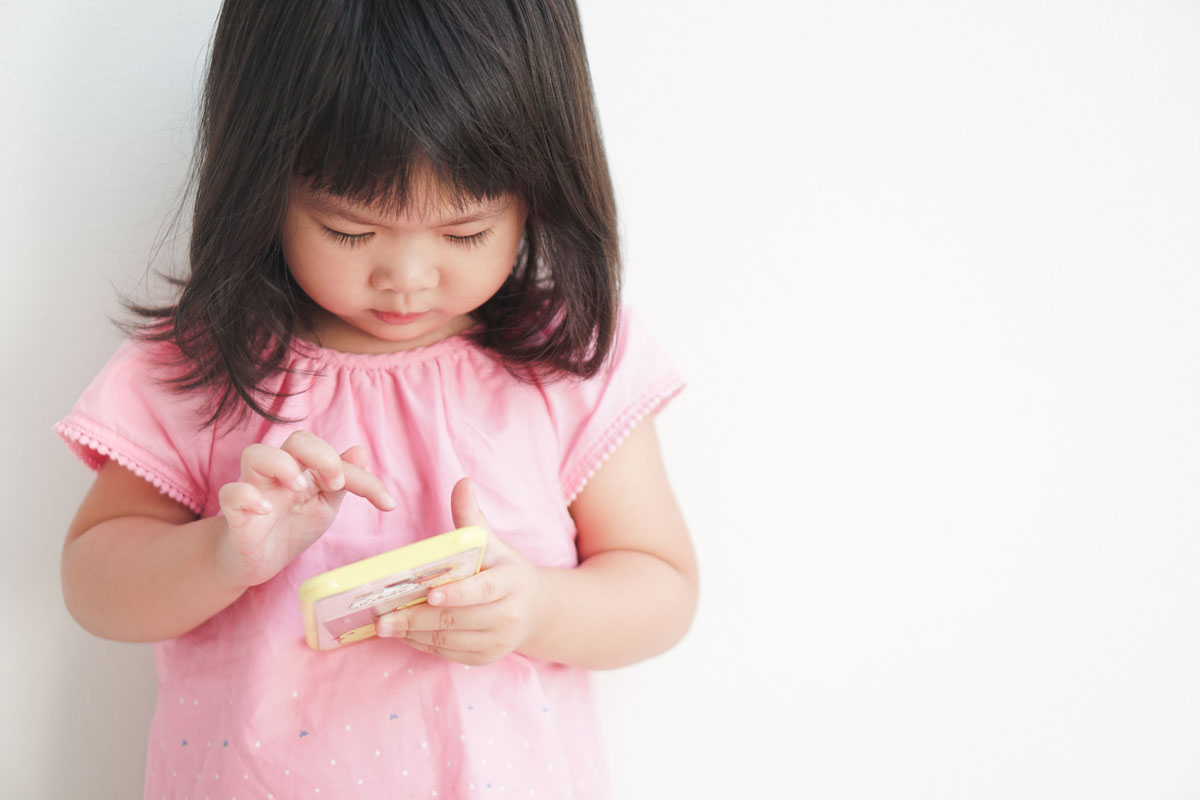 young toddler playing with games on a cell phone