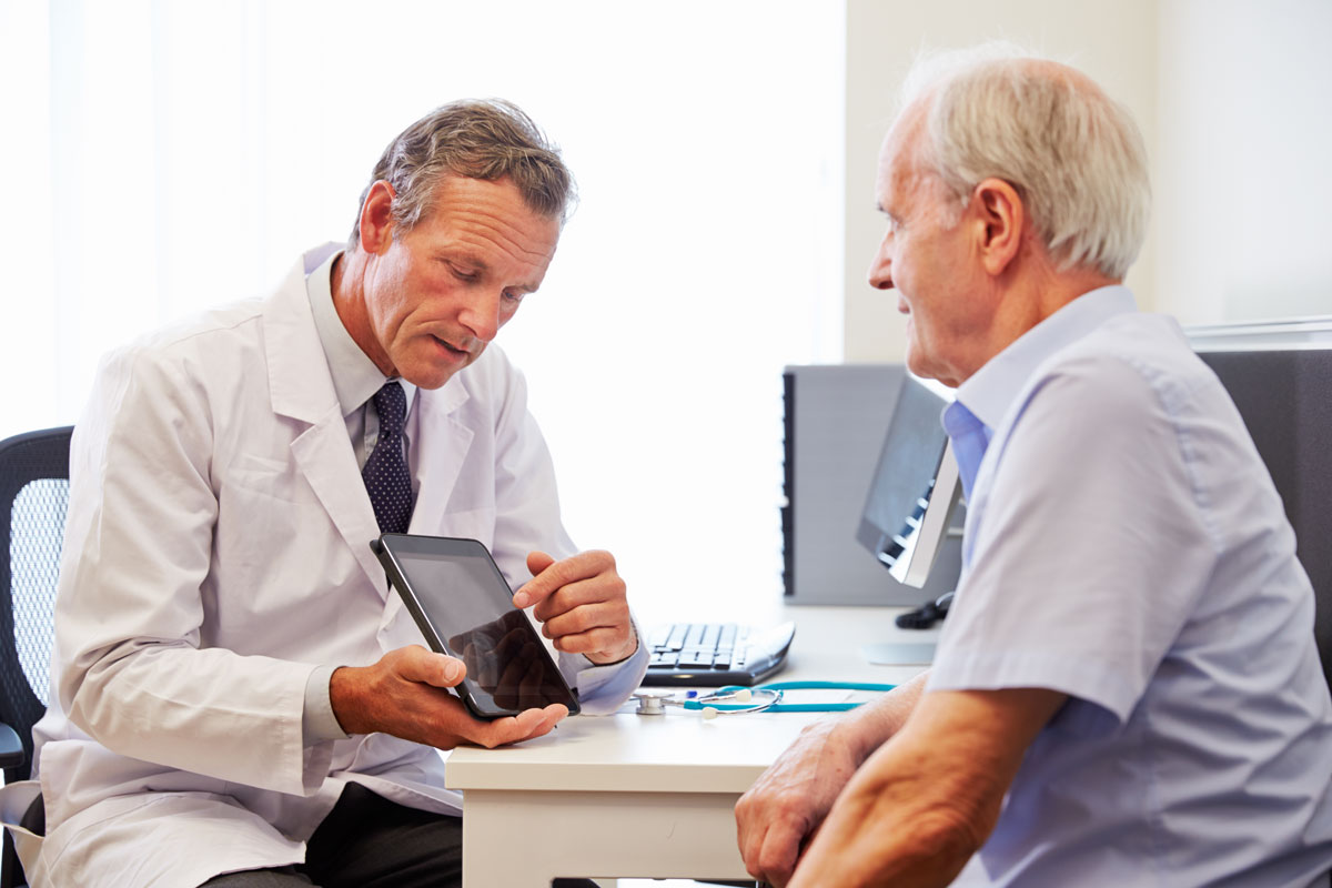 doctor discussing treatment options with elderly man